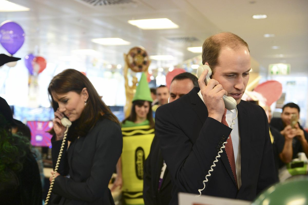 O príncipe William e Kate Middleton falam ao telefone num evento solidário em Londres (REUTERS/Jeremy Selwyn)