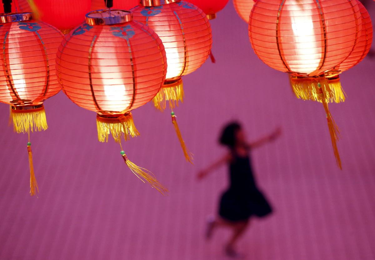 Uma criança brinca à luz das lanternas num templo chinês em Kuala Lumpur, Malásia (REUTERS/Olivia Harris)