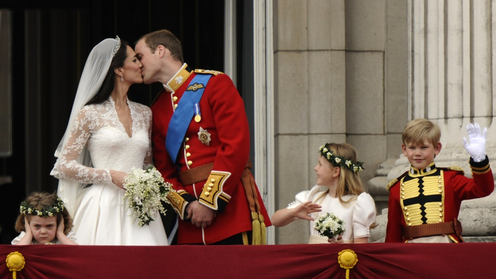 File photograph shows Britain's Prince William and his wife Catherine, Duchess of Cambridge kissing as they stand on the balcony at Buckingham Palace with other members of their families, after their wedding in Westminster Abbey, in central London