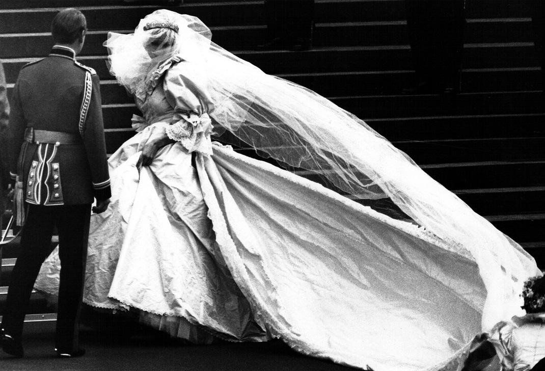 Lady Diana Spencer, soon to become the Princess of Wales, showing her wedding gown for the first time, turns as her bridesmaids set her train on arrival at Saint Paul's Cathedral for her wedding to Prince Charles in London