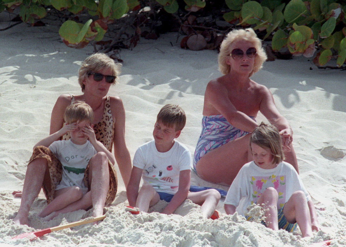 Princess Diana nurses Prince Harry on her lap as Prince William plays in the sand on a private beach on Necker Island in the British Virgin Islands