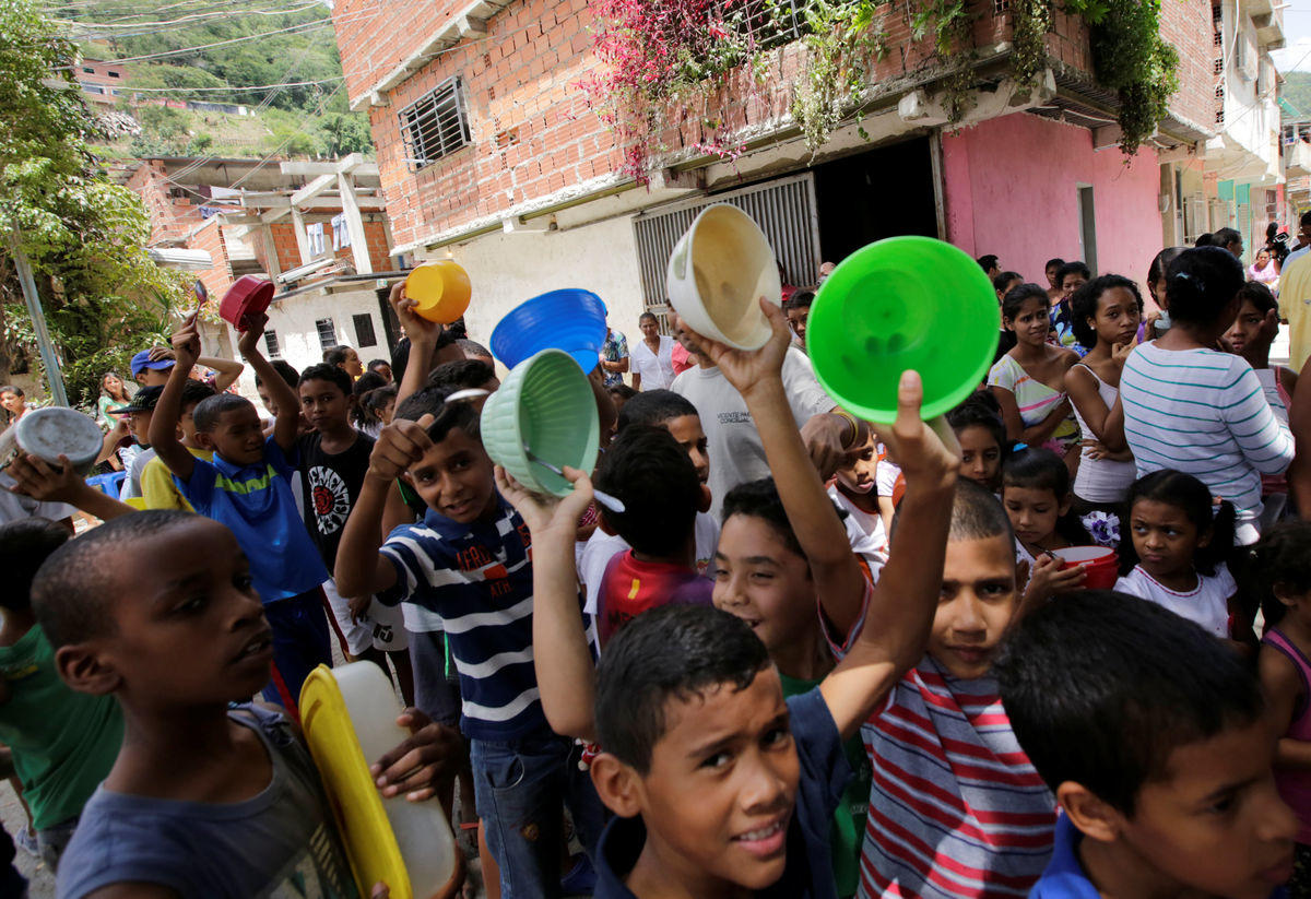 Children queue to wait to receive free food which was prepared by residents and volunteers on a street in the low-income neighborhood of Caucaguita in Caracas