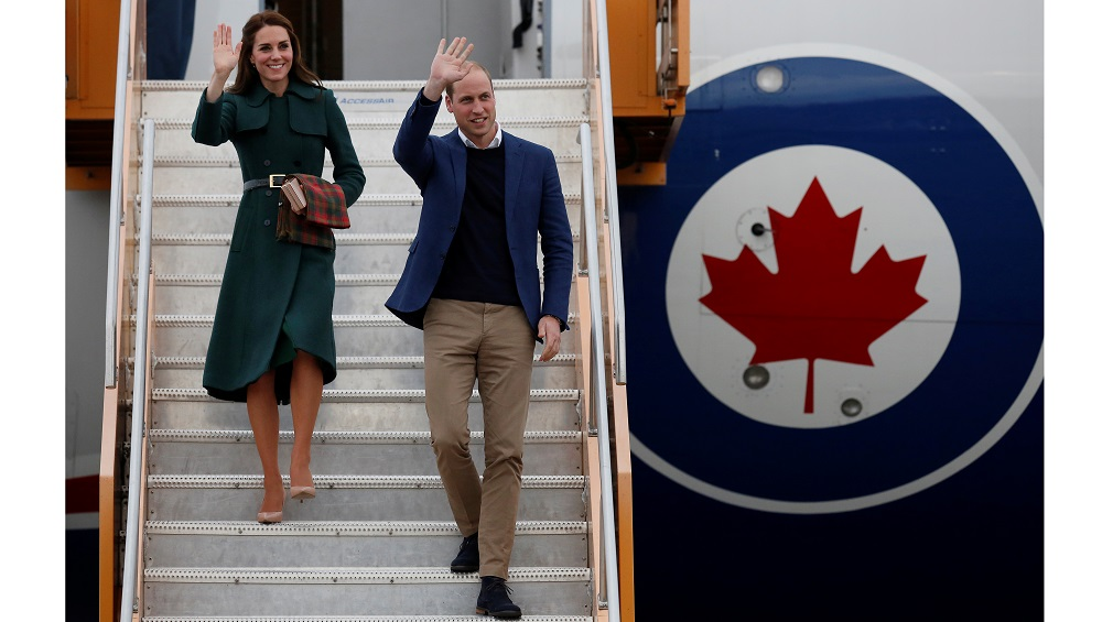 Britain's Prince William and Catherine, Duchess of Cambridge, wave as they arrive at the airport in Whitehorse