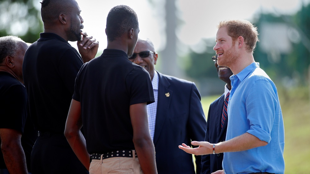 Prince Harry speaks with former cricket players as he arrives for a sporting event during his official visit in St. Johns
