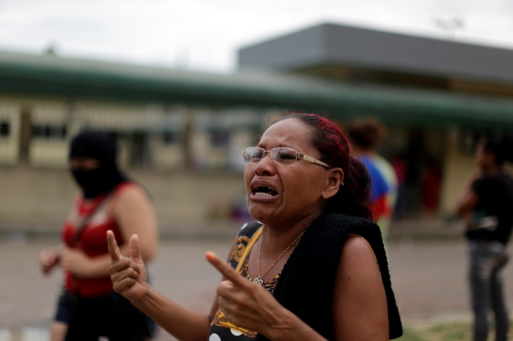 A relative of a prisoner reacts in front of the main entrance of Anisio Jobim prison in Manaus