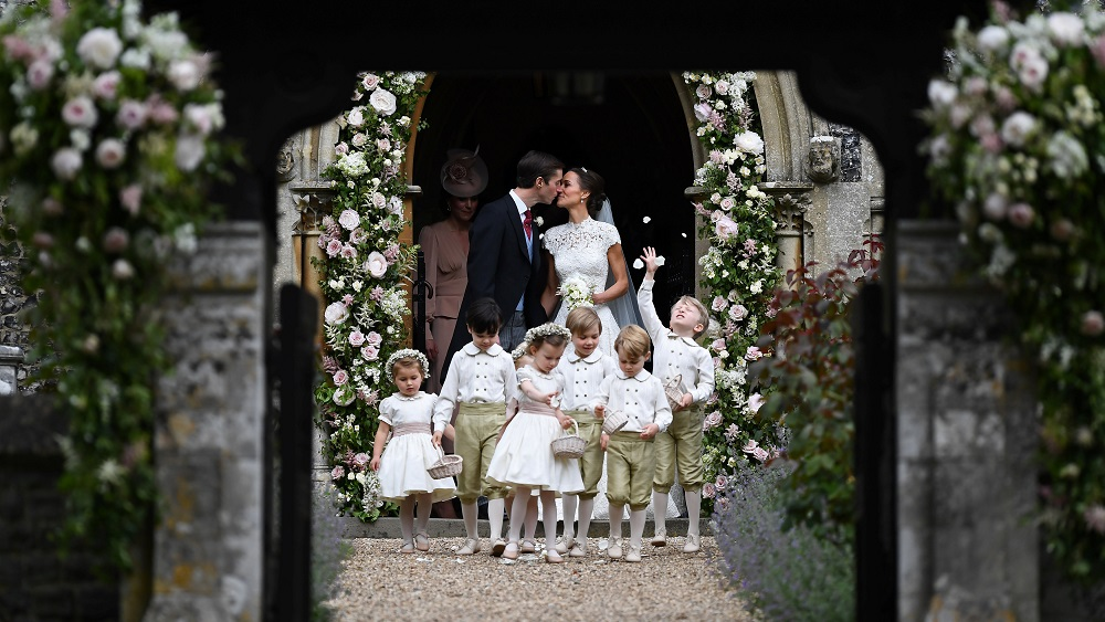 Pippa Middleton kisses her new husband James Matthews, following their wedding ceremony at St Mark's Church, as the bridesmaids, including Britain's Princess Charlotte and pageboys, including Prince George, walk ahead, in Englefield