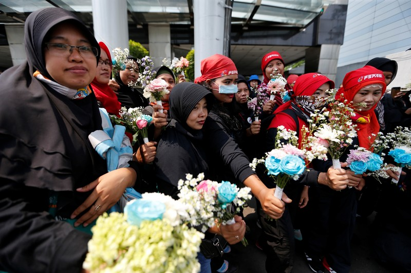 Indonesian workers hold flowers as they pose during a May Day rally in Jakarta